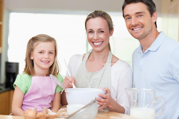 Fille préparant la pâte avec ses parents