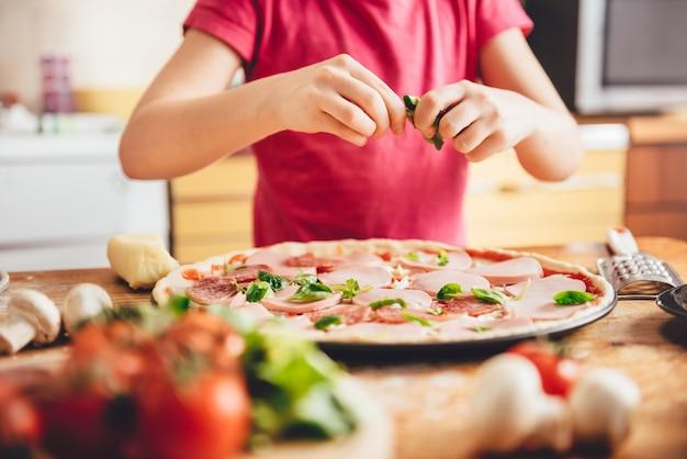 Fille préparant une pizza