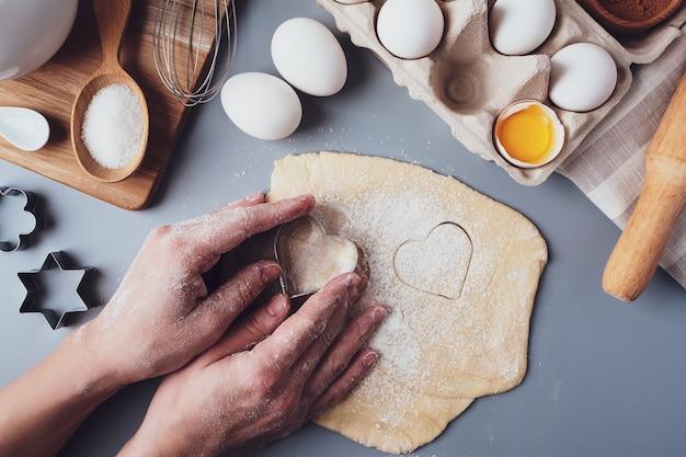 Fille prépare des biscuits en forme de coeur, composition à plat sur fond gris. emporte-pièces et pâte dans les mains des femmes. concept de nourriture pour la saint-valentin, la fête des pères, la fête des mères.