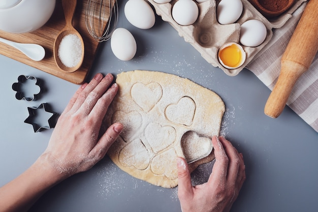 Fille prépare des cookies en forme de coeur, composition laïque plat sur fond gris.