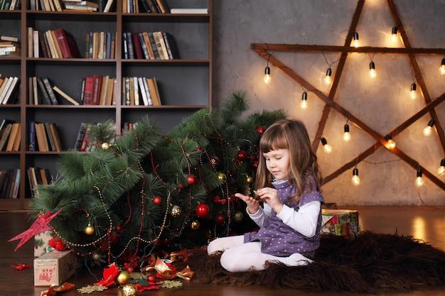 Fille près d'un arbre de noël tombé