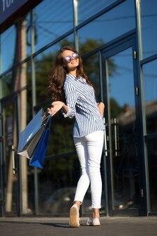 Une fille près du mur d'un centre commercial.