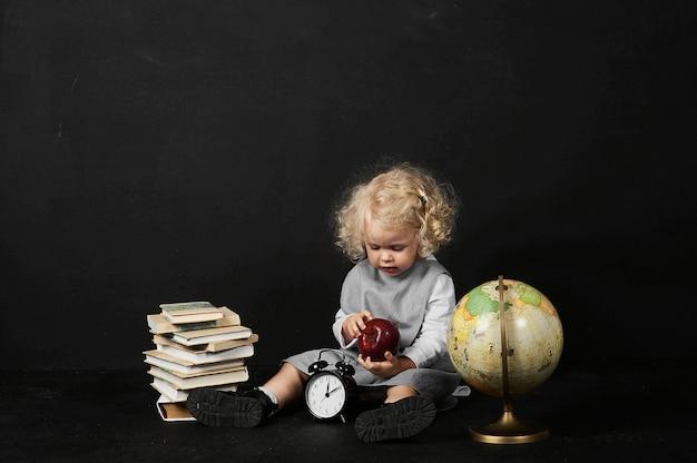 Fille préscolaire heureuse avec un livre, globe et horloge sur fond noir