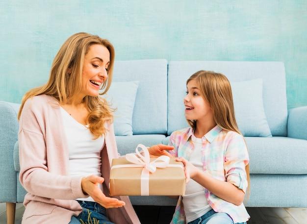 Fille présentant un coffret cadeau pour mère