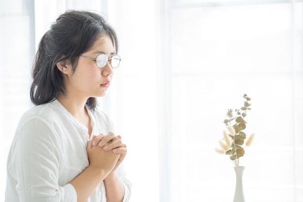 La fille de prière adore dieu et prie de chez elle pour le coronavirus covid-19. prier à la maison, église en ligne, mains en prière, culte à la maison