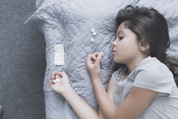 Une fille a pris une grande dose de comprimés et se couche sur son lit