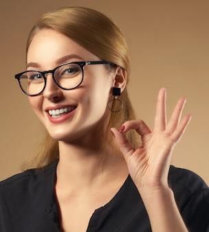 Fille professionnelle heureuse portant des lunettes et tenant la tablette isolé sur fond marron