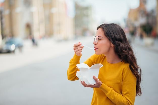 Fille profitant des plats à emporter dans la rue.