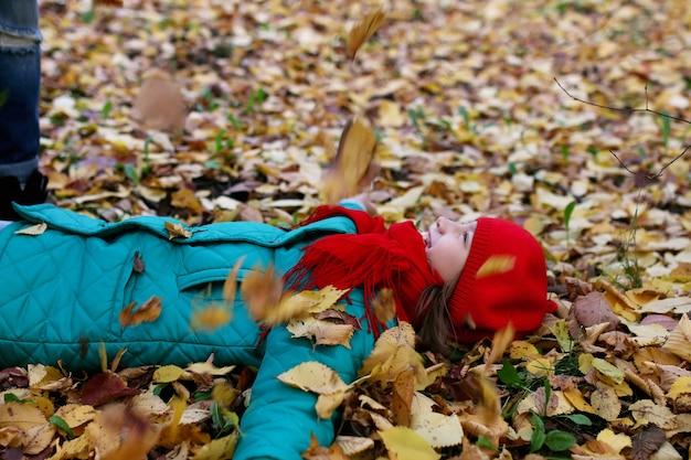 Fille sur une promenade dans un parc d'automne pendant une feuille d'automne