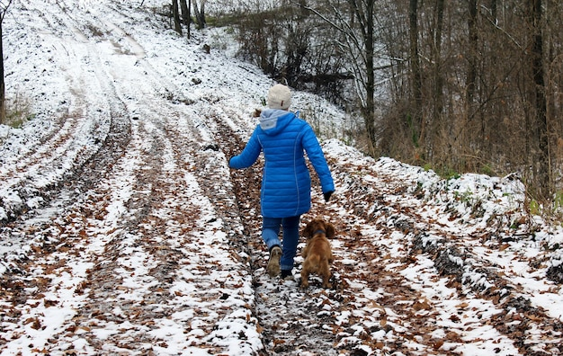La fille promène son chien dans la première neige