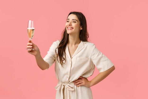 Fille prononçant un discours au cours de la partie de bachelorette. enthousiaste et heureuse souriante jeune femme insouciante en robe, soulevant le verre de champagne en riant et souriant, félicitant avec anniversaire, mur rose