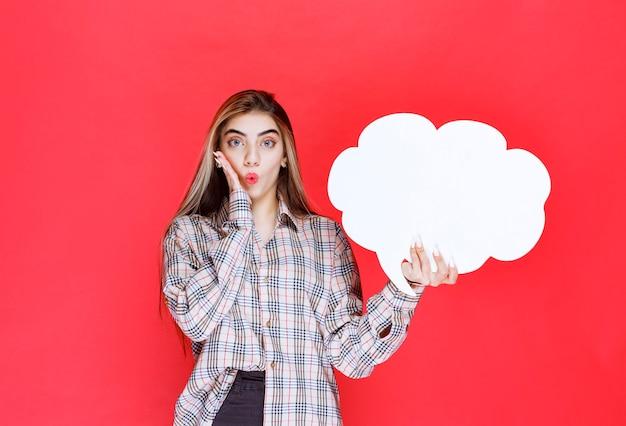 Fille en pull chaud tenant un tableau d'idées en forme de nuage et a l'air surprise