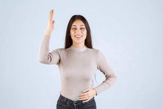 Fille en pull gris levant les mains.