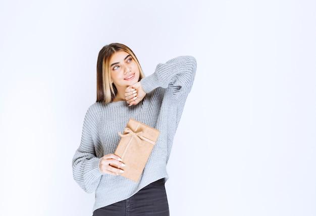Fille en pull gris tenant une boîte cadeau en carton.