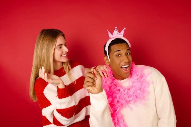 Une fille en pull rayé mettant une couronne sur la tête de son petit ami