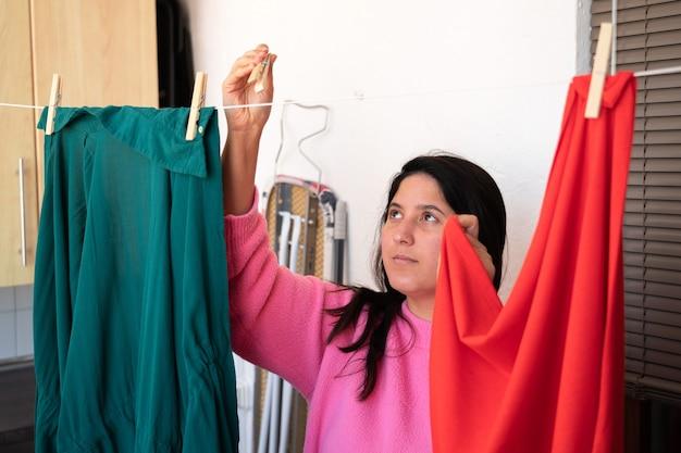 Fille avec un pull rose et des cheveux longs traîner des vêtements