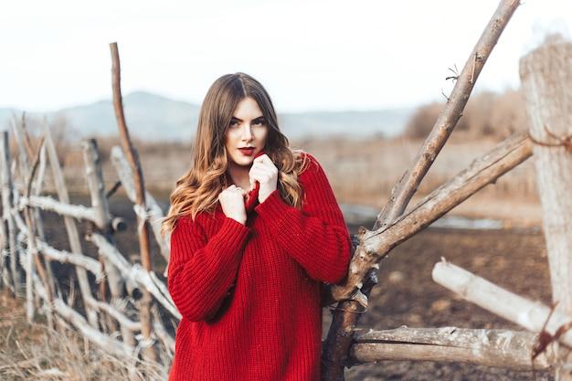 Fille en pull rouge en forêt