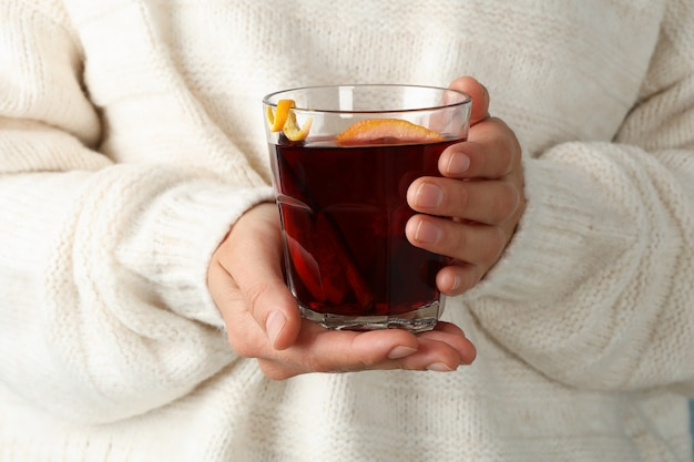 Fille en pull tenant le verre de vin chaud, gros plan