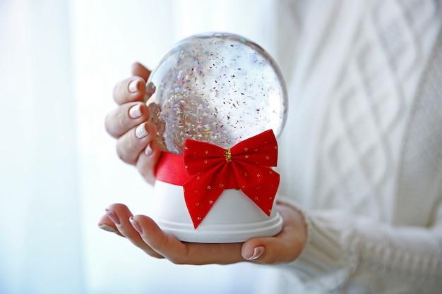 Fille en pull tricoté tenant une boule à neige avec un arc rouge