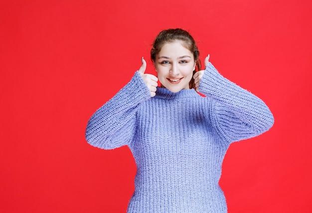 Fille en pull violet se sentant heureuse et positive.