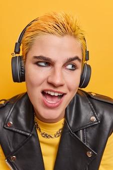 Une fille punk positive aux cheveux jaunes courts, au maquillage foncé vêtue de vêtements à la mode, écoute de la musique dans des écouteurs sans fil et profite d'un podcast audio pour se divertir