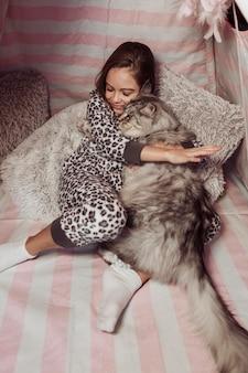 Fille en pyjama et chat étreignant