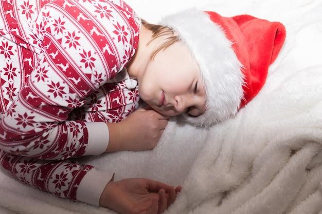 Une fille en pyjama du nouvel an et une casquette de père noël dort doucement