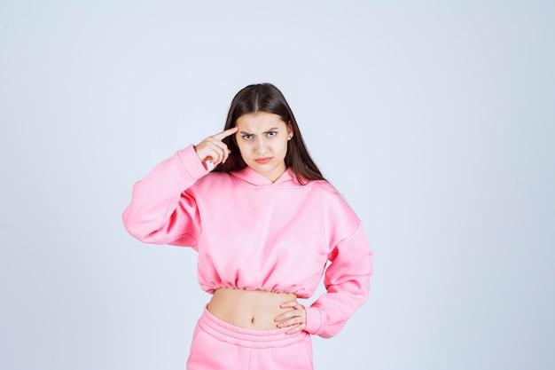 Fille en pyjama rose a l'air confuse et réfléchie