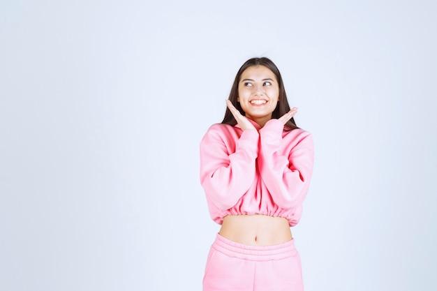 Fille en pyjama rose donnant des poses méchantes et gaies