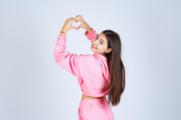Fille en pyjama rose envoi d'amour