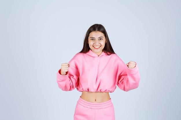 Fille en pyjama rose est une gagnante et montre ses poings