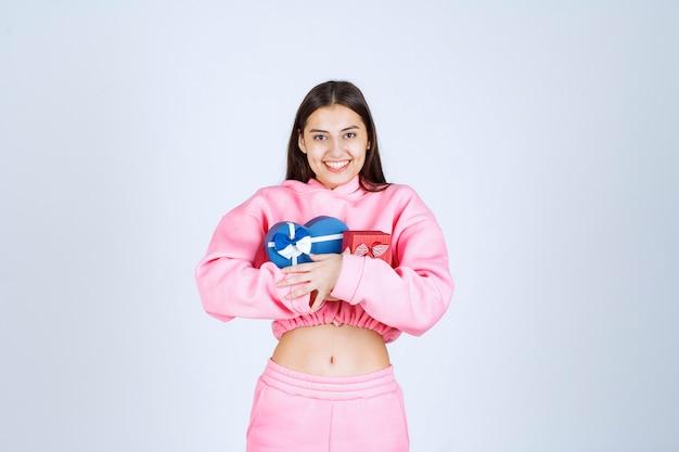 Fille en pyjama rose étreignant des coffrets cadeaux en forme de coeur rouge et bleu.