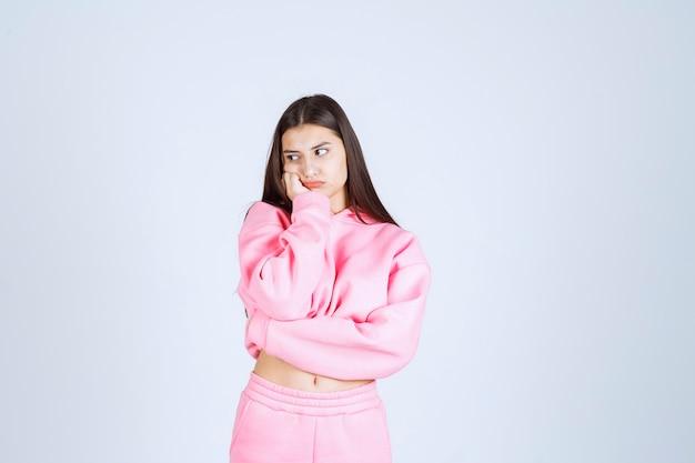 Fille en pyjama rose faisant visage très agressif et en colère