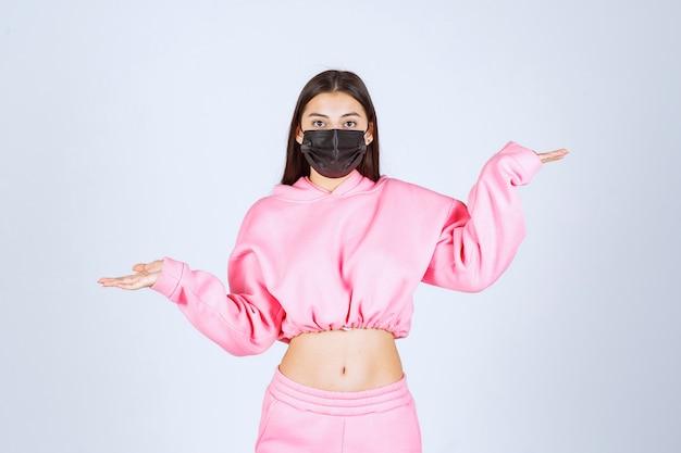Fille en pyjama rose et masque noir pointant vers la gauche.