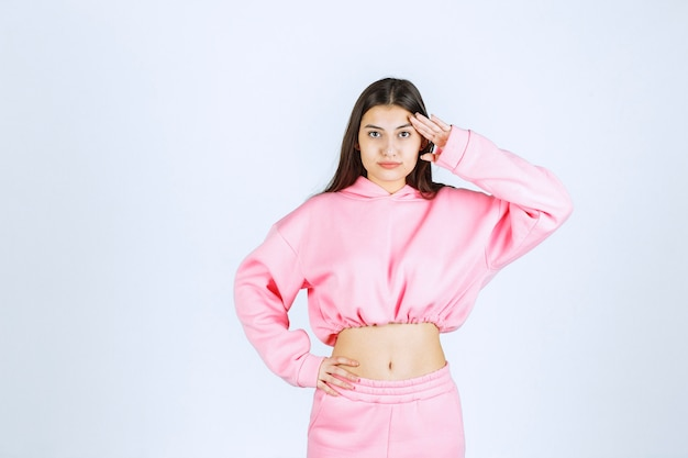 Fille en pyjama rose mettant les doigts sur son front