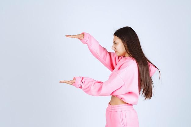 Fille en pyjama rose montrant la quantité ou la taille estimée d'un produit