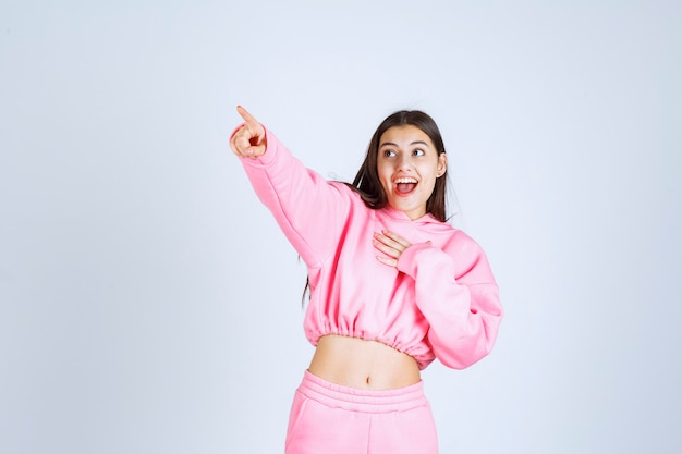 Fille en pyjama rose montrant quelque chose sur la gauche