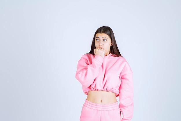 Fille en pyjama rose pensant et analysant