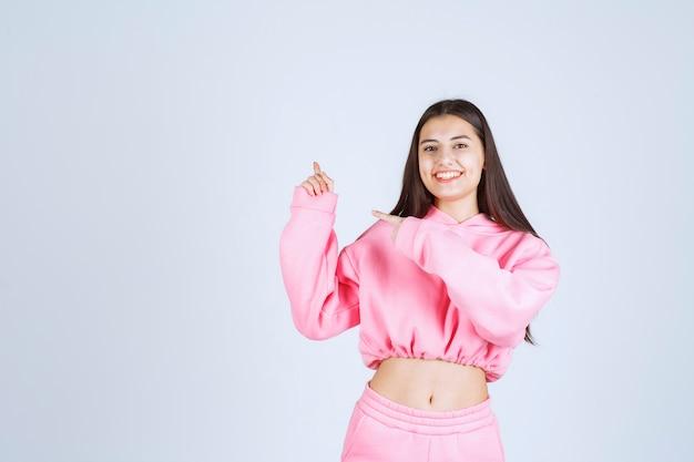 Fille en pyjama rose pointant vers le haut