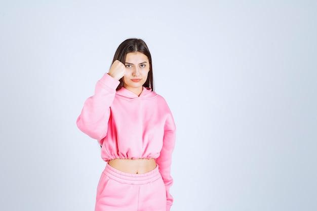 Fille en pyjama rose ressemble à un combattant et agressif