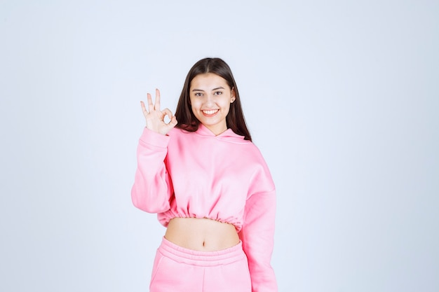 Fille en pyjama rose se sent heureuse et montre un signe de main positif.