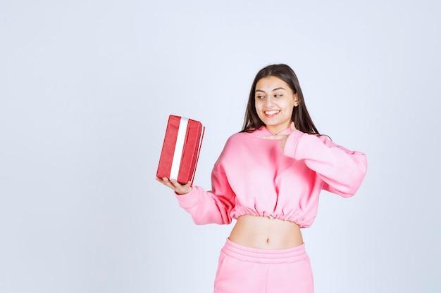 Fille en pyjama rose tenant une boîte-cadeau rectangulaire rouge et semble satisfaite.