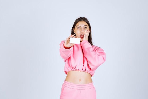 Fille en pyjama rose tenant une carte de visite et a l'air excitée.