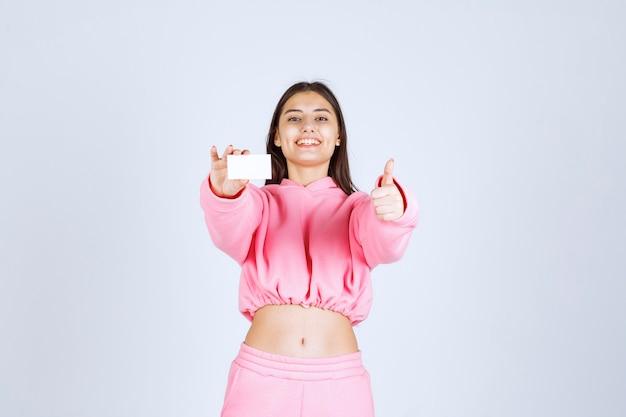 Fille en pyjama rose tenant une carte de visite et montrant le signe de la main de plaisir.