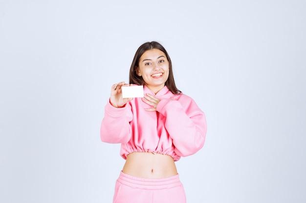 Fille en pyjama rose tenant une carte de visite et pointant sur elle-même.