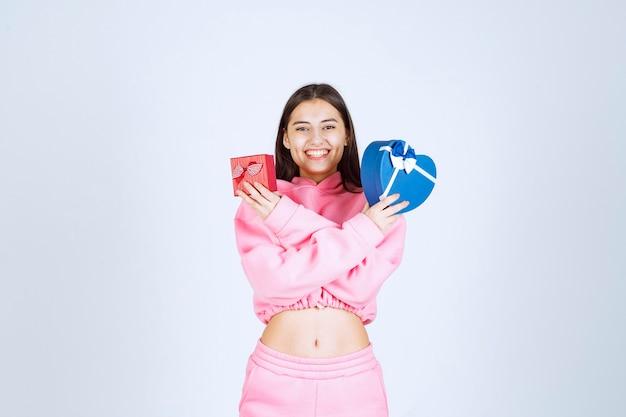 Fille en pyjama rose tenant des coffrets cadeaux en forme de coeur rouge et bleu dans les deux mains.