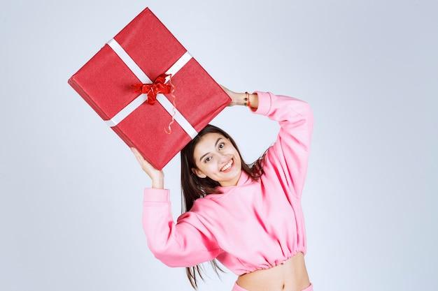 Fille en pyjama rose tenant une grande boîte-cadeau rouge au-dessus de sa tête.