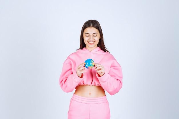 Fille en pyjama rose tenant un mini globe dans sa main.