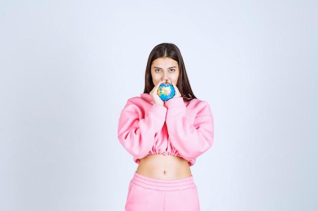 Fille en pyjama rose tenant un mini globe entre ses mains.