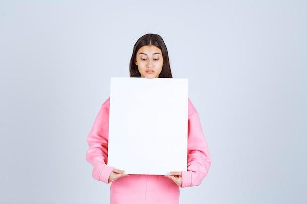 Fille en pyjama rose tenant un panneau de présentation carré blanc devant elle.